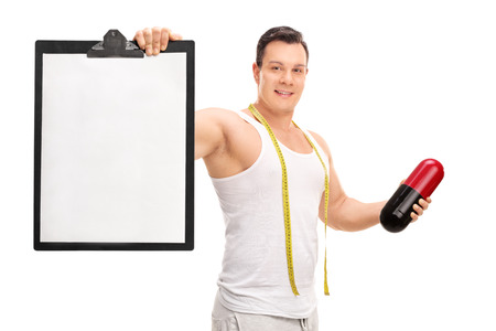 it is isolated: Young man holding a big diet pill and a clipboard with a blank sheet on it isolated on white background
