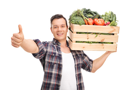 posing  agree: Young agricultural worker carrying a crate full of vegetables and giving a thumb up isolated on white background