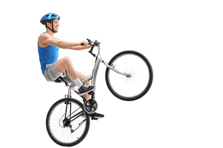 wheelie: Young cyclist performing a wheelie with a bicycle isolated on white background Stock Photo