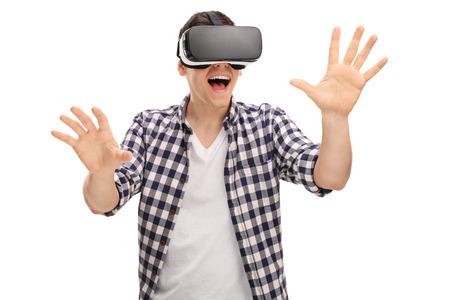 VR のヘッドセットを介して仮想現実を経験し、白い背景に分離された彼の手で何かに触れて興奮男