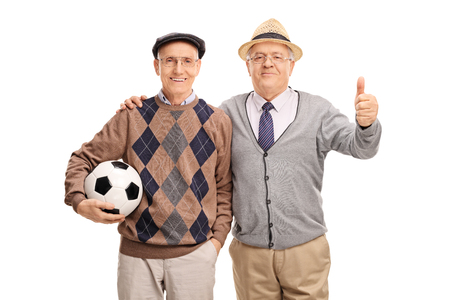 posing  agree: Studio shot of two senior gentlemen holding a football and giving a thumb up isolated on white background