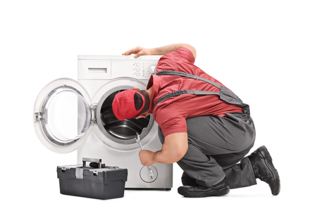 machines: Young repairman examining a washing machine and holding a wrench isolated on white background