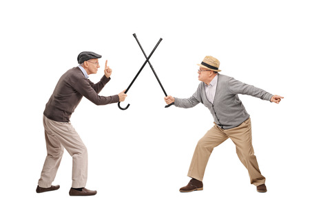Studio shot di due signori anziani che hanno una lotta spada con i loro bastoni isolato su sfondo bianco Archivio Fotografico