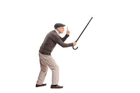 Retrato de cuerpo entero de un hombre mayor enfurecido sosteniendo su bastón como una espada y amenazando a alguien aislada en el fondo blanco Foto de archivo