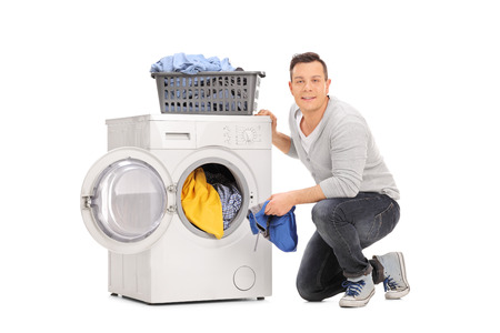 emptying: Studio shot of a cheerful young man doing laundry and looking at the camera isolated on white background Stock Photo