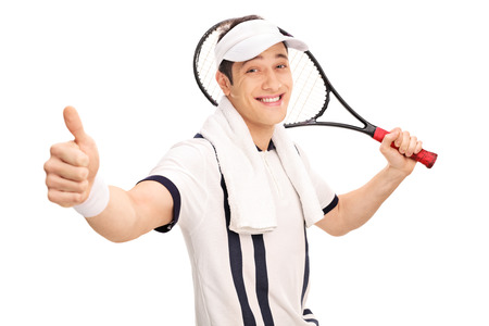 posing  agree: Cheerful tennis player holding a racket and giving a thumb up isolated on white background