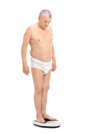 man underwear: Full length portrait of a senior man in white underwear standing on a weight scale and measuring his weight isolated on white background Stock Photo