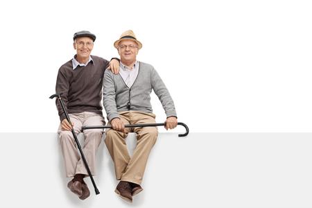 hombre sentado: Dos amigos mayor que sostiene los bastones y se sientan en un letrero blanco en blanco aislado en fondo blanco