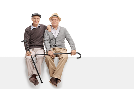 Dwóch starszych kumpli trzymając laski i siedzi na pustym białym szyld na białym tle