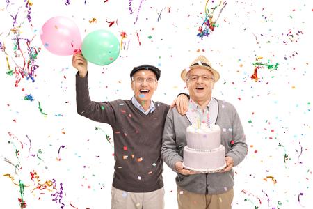 serpentinas: Dos señores mayores que celebran cumpleaños con un pastel y globos aislados sobre fondo blanco