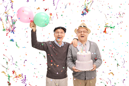 Two senior gentlemen celebrating birthday with a cake and balloons isolated on white background
