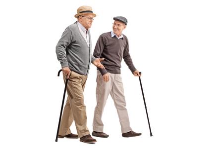 caminando: Dos señores mayores que recorren y que hablan el uno al otro aislado en el fondo blanco