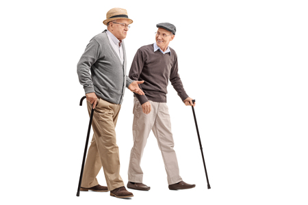 elderly adults: Two senior gentlemen walking and talking to each other isolated on white background Stock Photo