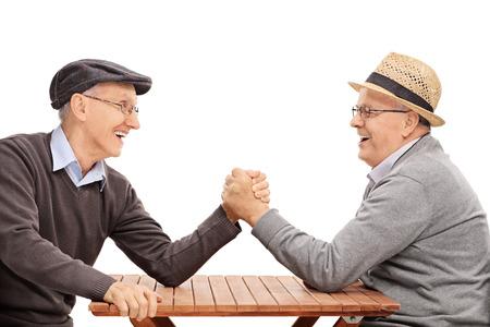 Dos hombre mayor que tiene un concurso brazo luchar sentado en una mesa aislada en el fondo blanco Foto de archivo - 53467127