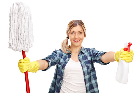 housewife gloves: Young woman holding a mop and a spray and preparing to clean isolated on white background