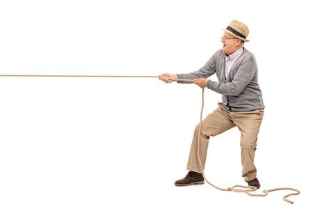 Studio foto de una mayor alegre tira de una cuerda aislada en el fondo blanco