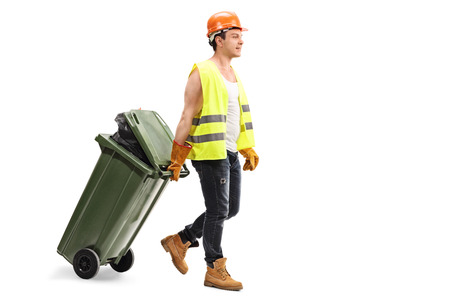 dragging: Full length portrait of a male waste collector dragging a trash can isolated on white background