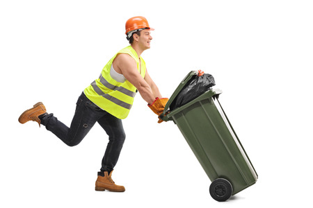 collector: Excited young waste collector pushing a trash can and running isolated on white background
