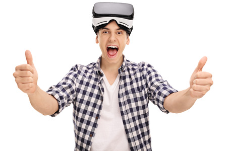 posing  agree: Joyful man giving two thumbs up after using a VR headset isolated on white background