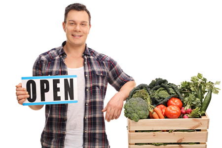 farmers market: Young market vendor holding an open sign next to a crate full of vegetables isolated on white background