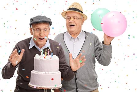 白い背景で隔離のケーキ、誕生日にろうそくを吹いて 2 興奮して上級紳士 写真素材