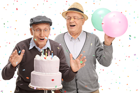 Two excited senior gentlemen blowing candles on a birthday cake isolated on white background