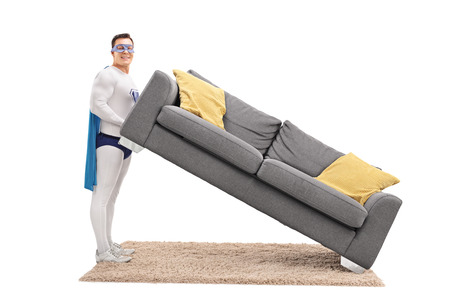 lifting: Young man in superhero costume lifting a sofa and looking at the camera isolated on white background