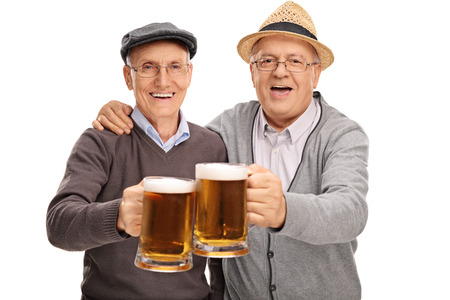 pilsner beer: Two senior gentlemen making a toast with beer and looking at the camera isolated on white background Stock Photo
