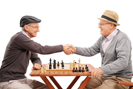 happy seniors: Two senior gentlemen shaking hands after playing a game of chess isolated on white background Stock Photo