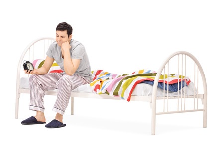 man sit: Sleepy young guy in pajamas sitting on bed and looking at the alarm clock isolated on white background