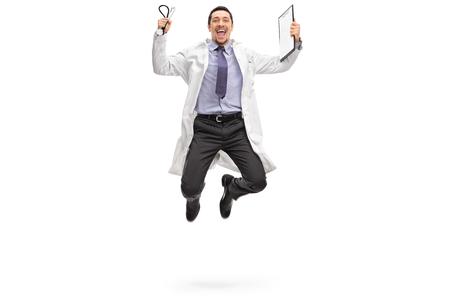 brincando: Retrato de cuerpo entero de un joven médico saltando de alegría aislada en el fondo blanco