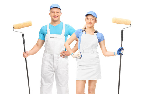 studio happy overall: Male and a female decorators holding paint rollers and posing in white uniforms isolated on white background Stock Photo