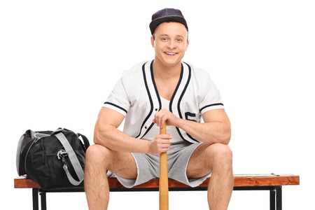 player bench: Young baseball player sitting on a bench and holding a baseball bat isolated on white background Stock Photo