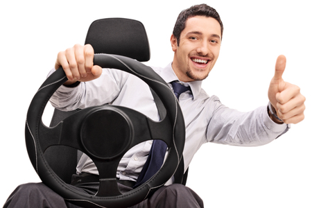 Young guy driving and giving a thumb up isolated on white background