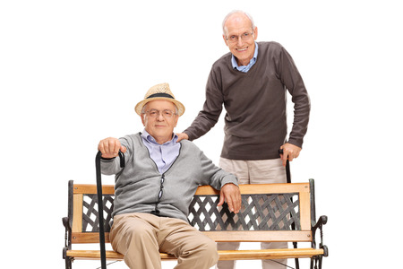 retirement happy man: Two senior old friends posing together seated on a wooden bench isolated on white background Stock Photo