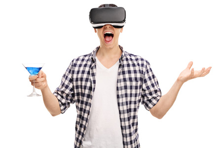 visualizing: Joyful man using a VR headset and holding a bright blue cocktail isolated on white background