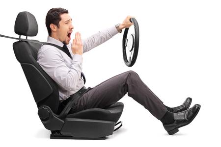 tiro de perfil de un individuo joven que sostiene un sueño volante sentado en un asiento de coche aislado en el fondo blanco