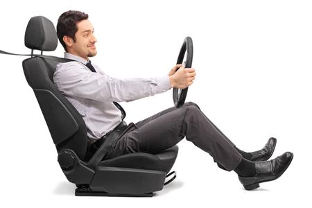 Profil Schuss eines jungen Mannes mit einem Lenkrad auf einem Autositz sitzt hält isoliert auf weißem Hintergrund