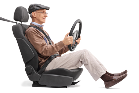 cautious: Senior holding a steering wheel seated on a car seat fastened with seatbelt isolated on white background Stock Photo