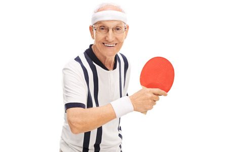 70s tennis: Cheerful senior man playing table tennis and looking at the camera isolated on white background Stock Photo