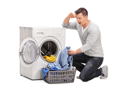 Studio shot of a displeased young man emptying a washing machine and looking at the clothes isolated on white background