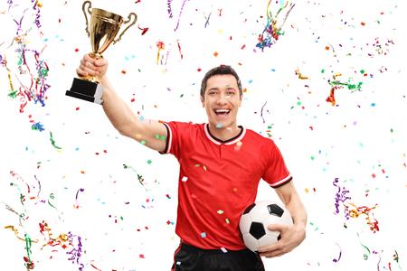 sportsman: jugador de fútbol alegre que sostiene un trofeo de oro y celebrando con serpentinas de confeti a su alrededor aisladas sobre fondo blanco