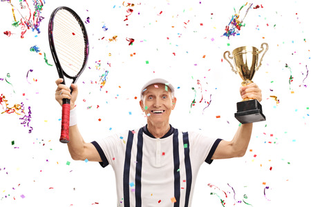 70s tennis: Joyful senior tennis player holding a trophy and celebrating victory isolated on white background