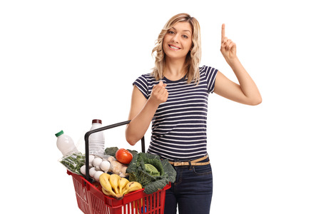 woman posing: Young woman holding a shopping basket full of groceries and having an idea isolated on white background