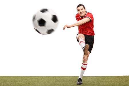 hombre disparando: Studio foto de una joven jugador de fútbol que golpea una bola en una superficie de hierba aislado sobre fondo blanco