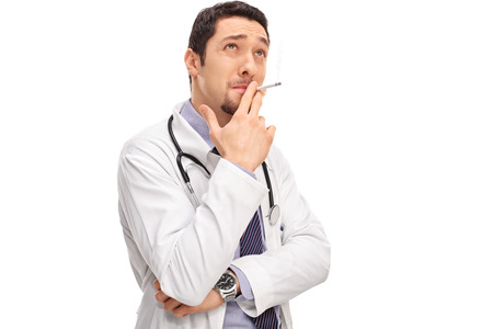 unprofessional: Young pensive doctor smoking a cigarette and looking up isolated on white background