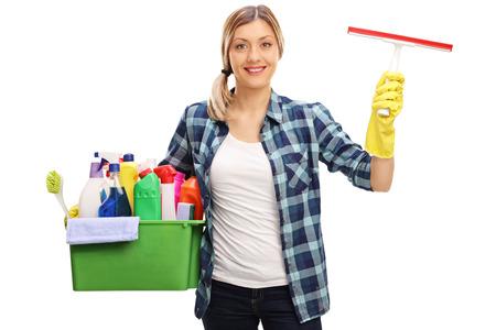 ama de casa: Mujer joven que sostiene un cubo lleno de equipos de limpieza y mirando a la c�mara aislada en el fondo blanco