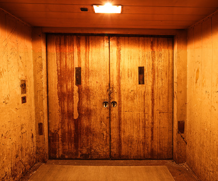 lift gate: Old and rusty closed elevator doors in a dark hallway Stock Photo