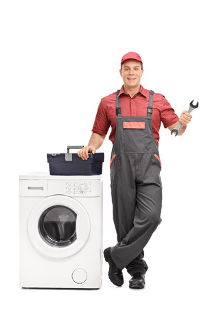 Full length portrait of a young repairman holding a wrench and standing next to a washing machine isolated on white background