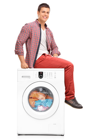 man laundry: Vertical shot of a young man waiting for the laundry seated on a washing machine isolated on white background